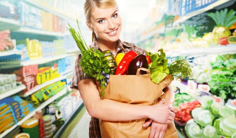 Kobieta na zakupach spożywczych z papierową torbą z warzywami i owocami. Dieta wegetariańska.