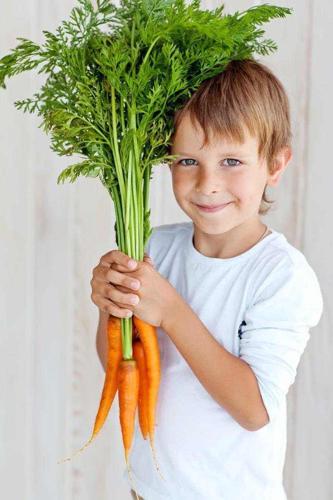 Chłopiec trzymający pęk świeżych marchewek.