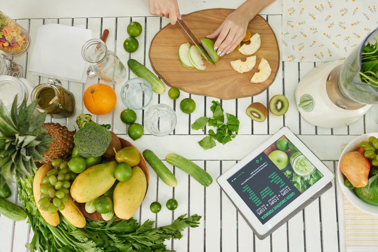 Kobieta przygotowująca smoothie ze świeżych warzyw i owoców.