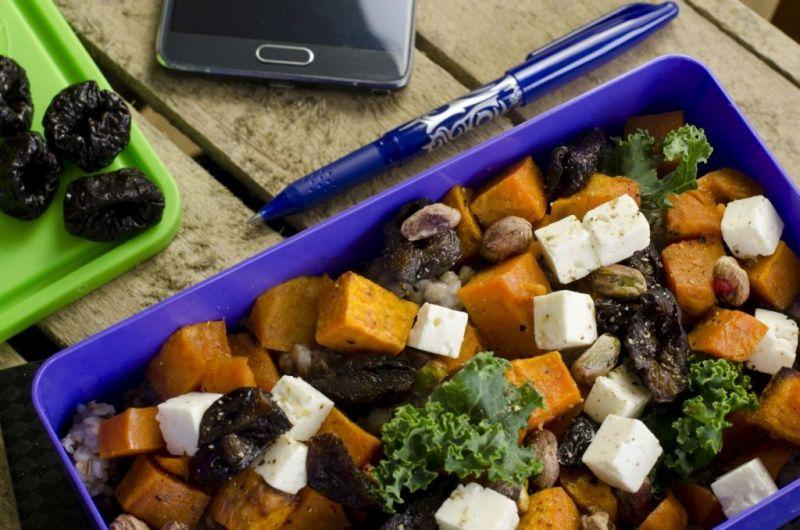 Sałatka z pieczonymi batatami, jarmużem i śliwką kalifornijską w lunchboxie. Obok leży długopis i smartphone.