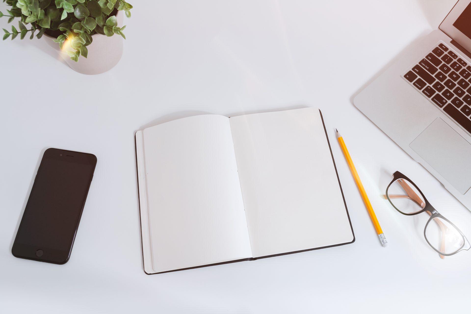 Widok na biurko z góry, na biurku otwarty notes, smartphone, ołówek, okulary, roślina doniczkowa i laptop.