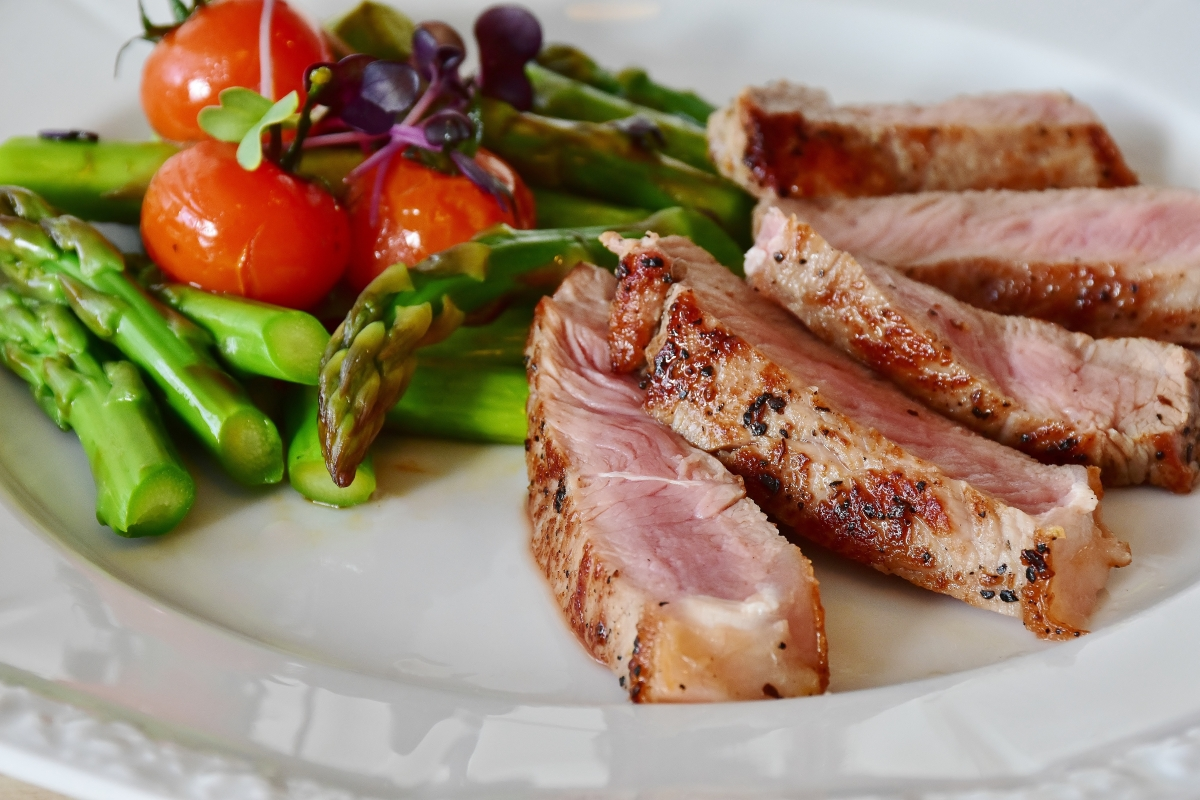 Zbliżenie na biały talerz. Na talerzu mięso pokrojone na kawałki, szparagi i pomidorki koktajlowe. Dieta rozdzielna, dieta niełączenia