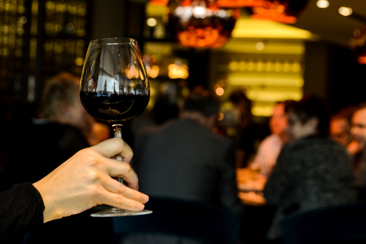 Ręka trzymająca kieliszek z czerwonym winem na tle restauracji.