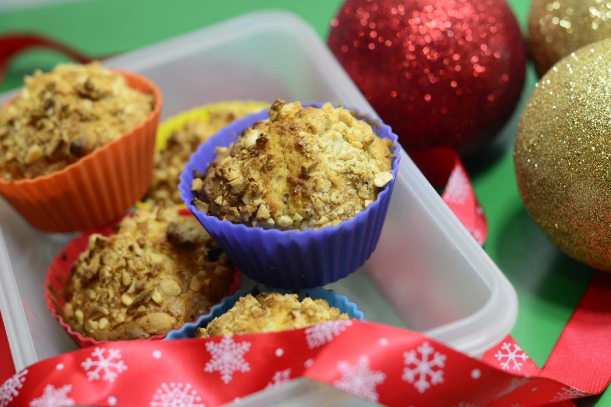 Muffinki z żurawiną w otoczeniu bombek i świątecznych wstążek ze śnieżynkami.