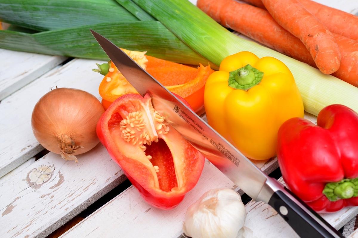 Warzywa na drewnianym tle. W paprykę wbity jest nóż, obok cebula, marchew i por. Dieta warzywno owocowa.