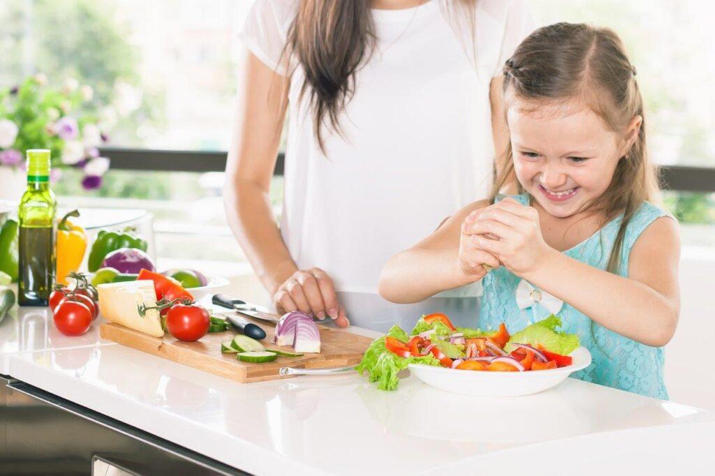 Mała dziewczynka gotuje z mamą zdrowy obiad. Dieta dziecka.