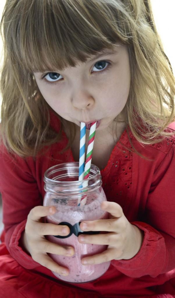 Dziewczynka pijąca smoothie z kaszą jaglaną i owocami