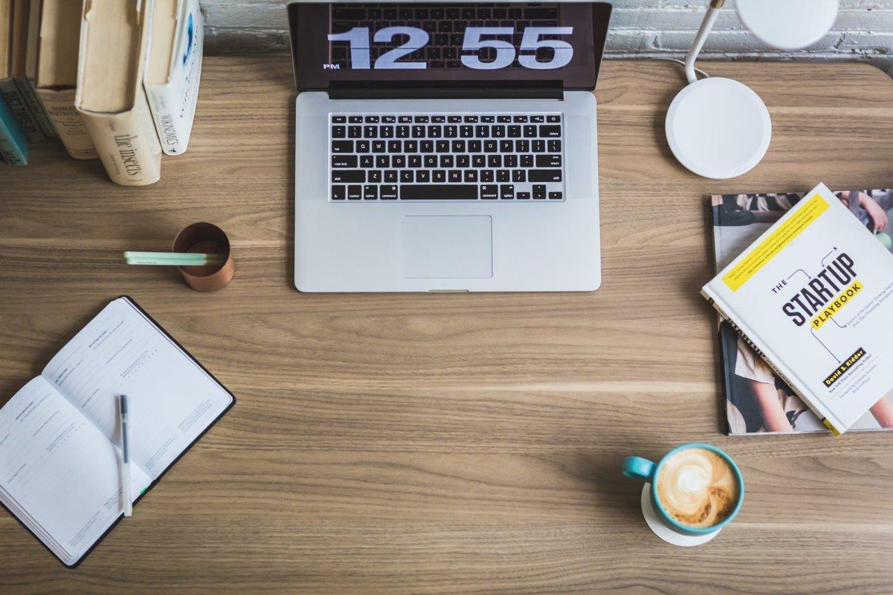Praca, biurko w pracy. Widok z bury na uporządkowane biurko z laptopem, książkami, kawą i notesem.