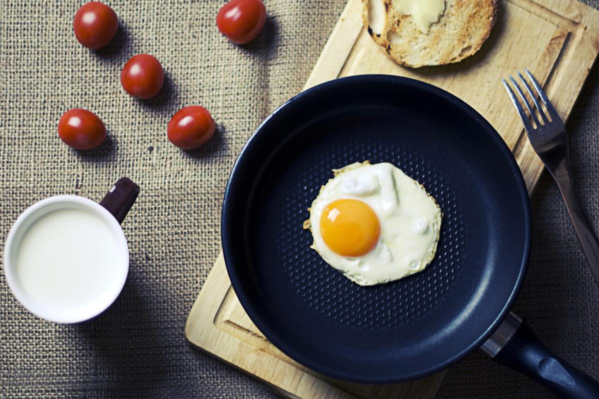 Jajko sadzone na patelni, obok pomidorki koktajlowe i kubek z mlekiem. Dieta kopenhaska.