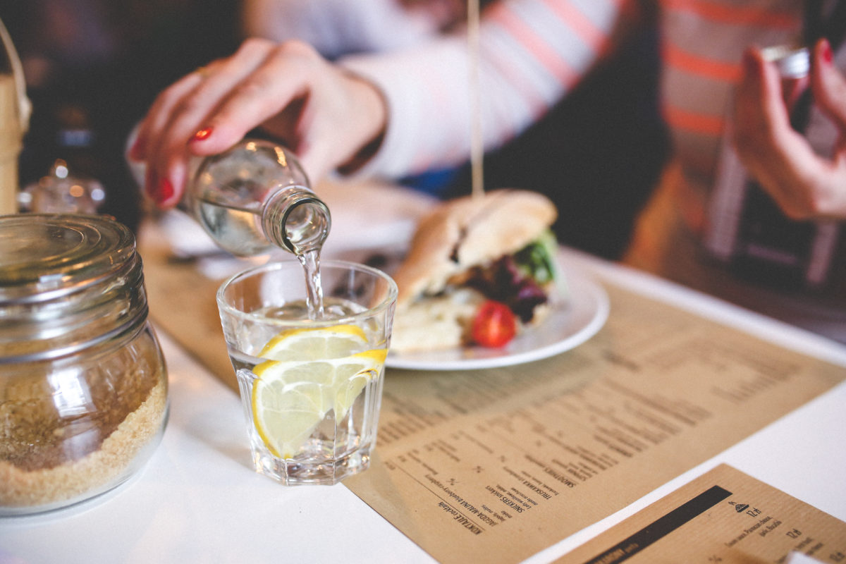 Lunch. Na stoliku w restauracji stoi szklanka wody z cytryną, widać też talerz z połową burgera.