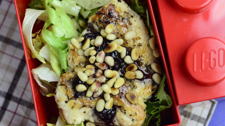 Kurczak z sosem porzeczkowym posypany orzeszkami pini, ułożony na sałacie. Kurczak w pojemniku typu lunchbox.