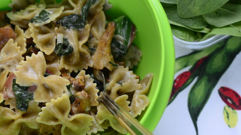 Makaron z kurkami, szpinakiem i kindziukiem w sosie serowym pokazany w zielonej misce. Ujęcie od góry.