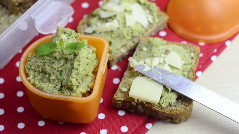 Pasta z bobu w małym pojemniki. Obok kromki chleba posmarowane pastą z bobu z plasterkami sera parmezan.