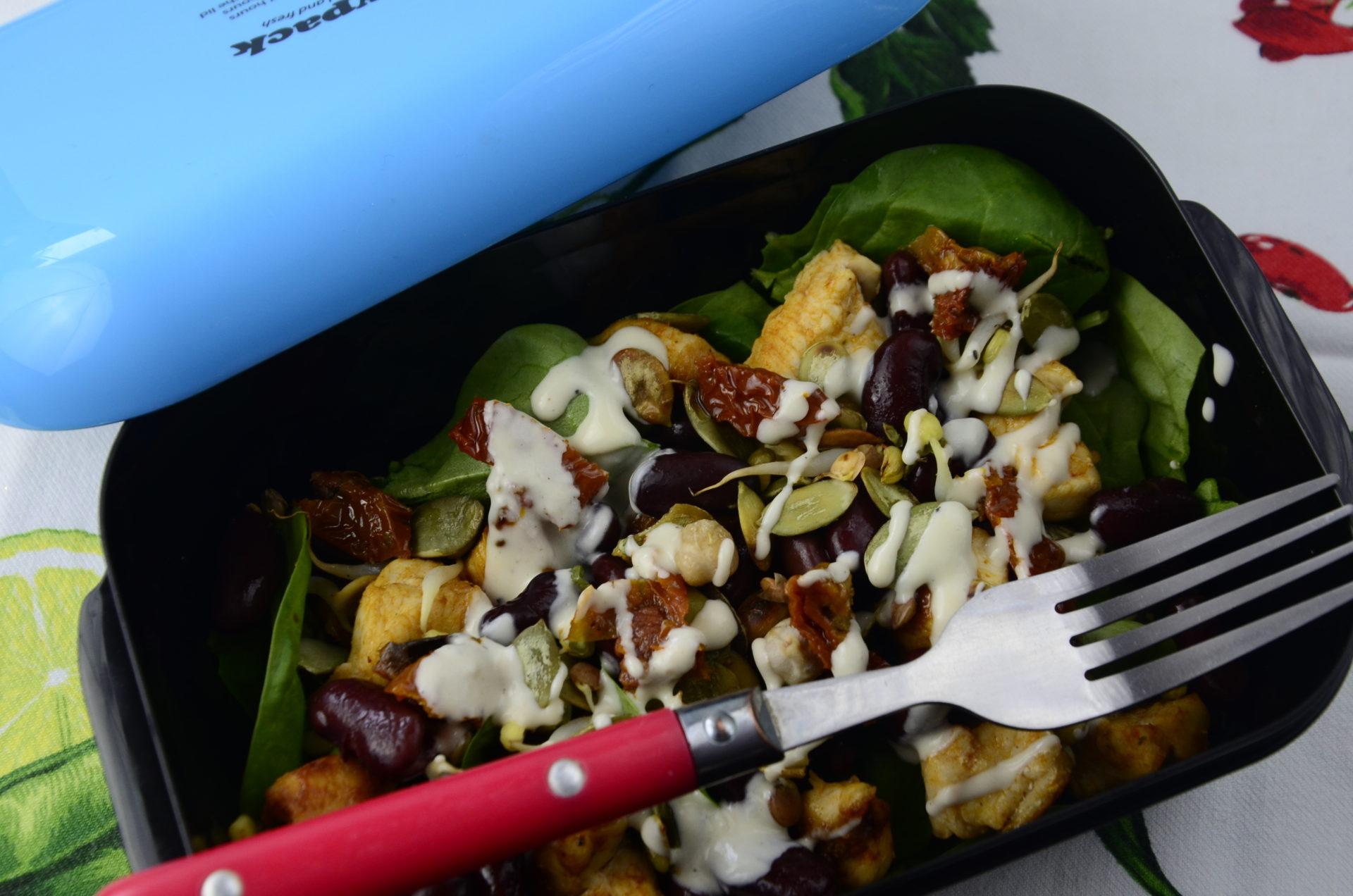Sałatka z sosem tahini spakowany z niebieski lunchbox.
