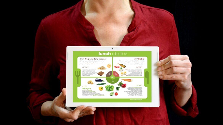 Kobieta trzymająca w ręku tablet, na tablecie wyświetlona infografika Lunch idealny.