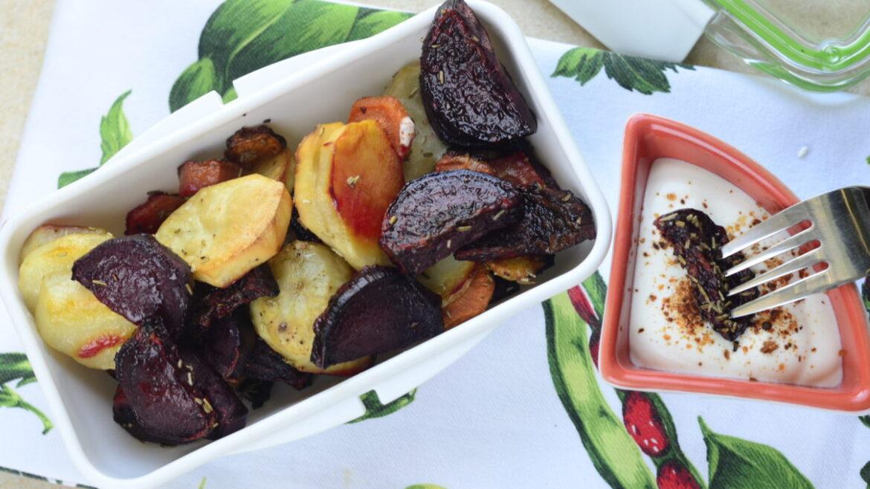 Pieczone warzywa - ziemniaki, marchew i buraki w lunchboxie. Obok sos jgurtowy.