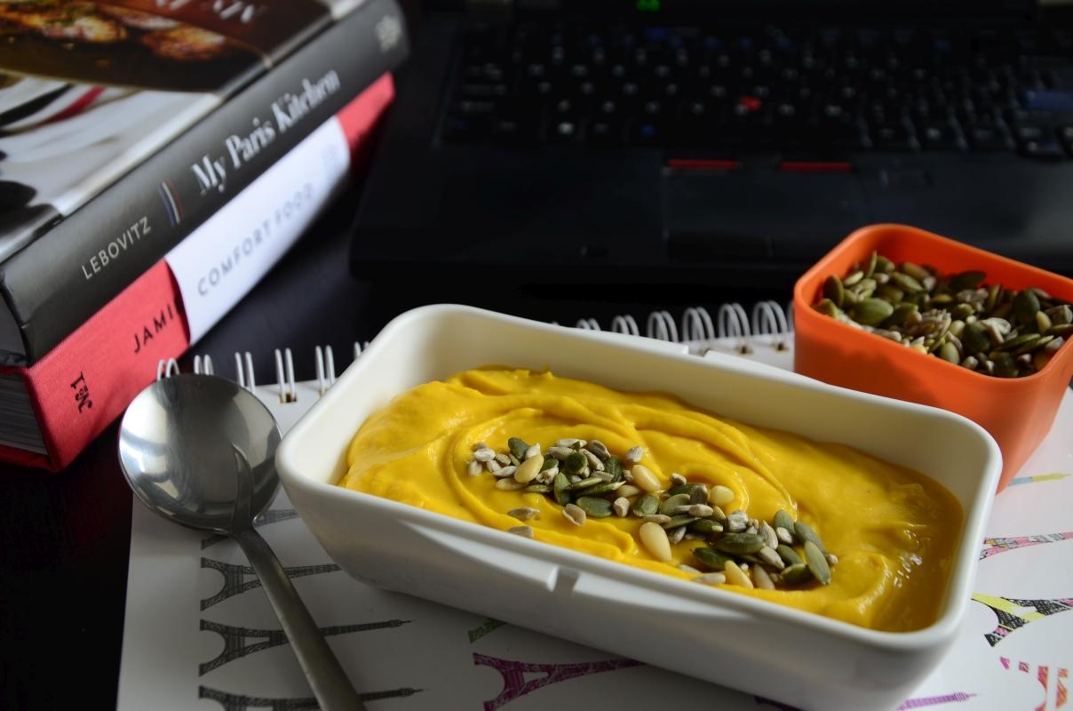 Zupa krem z dyni Hokkaido, z pestkami dyni, w lunchboxie. Widok na biurko, na biurku laptop, notes i książki.