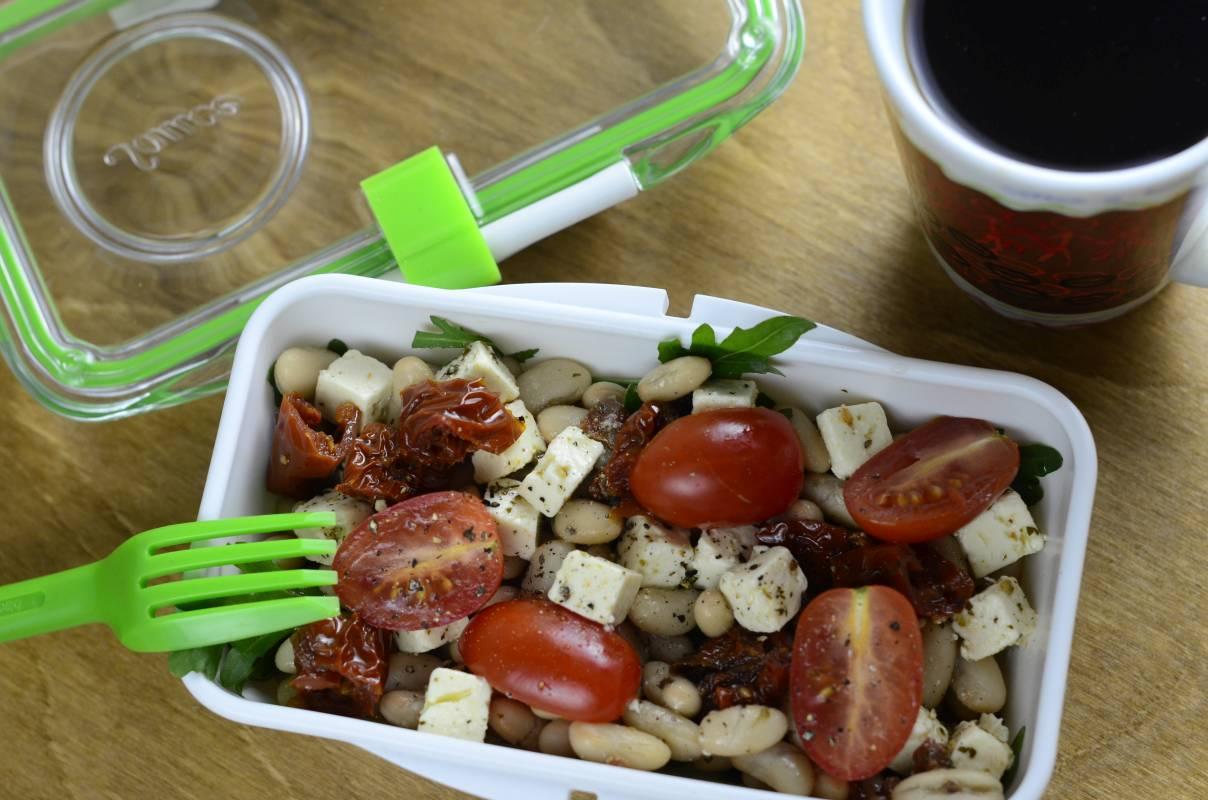 Sałatka z fetą i białą fasolą w lunchboxie. Danie na drewnianym blacie, obok kubek z kawą.
