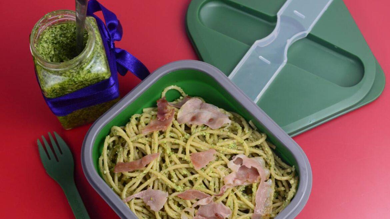 Spaghetti z pesto z rukolą i szynką parmeńską w zielonym lunchboxie. Obok widelec i słoiczek z pesto przewiązany wstążką niebieską.