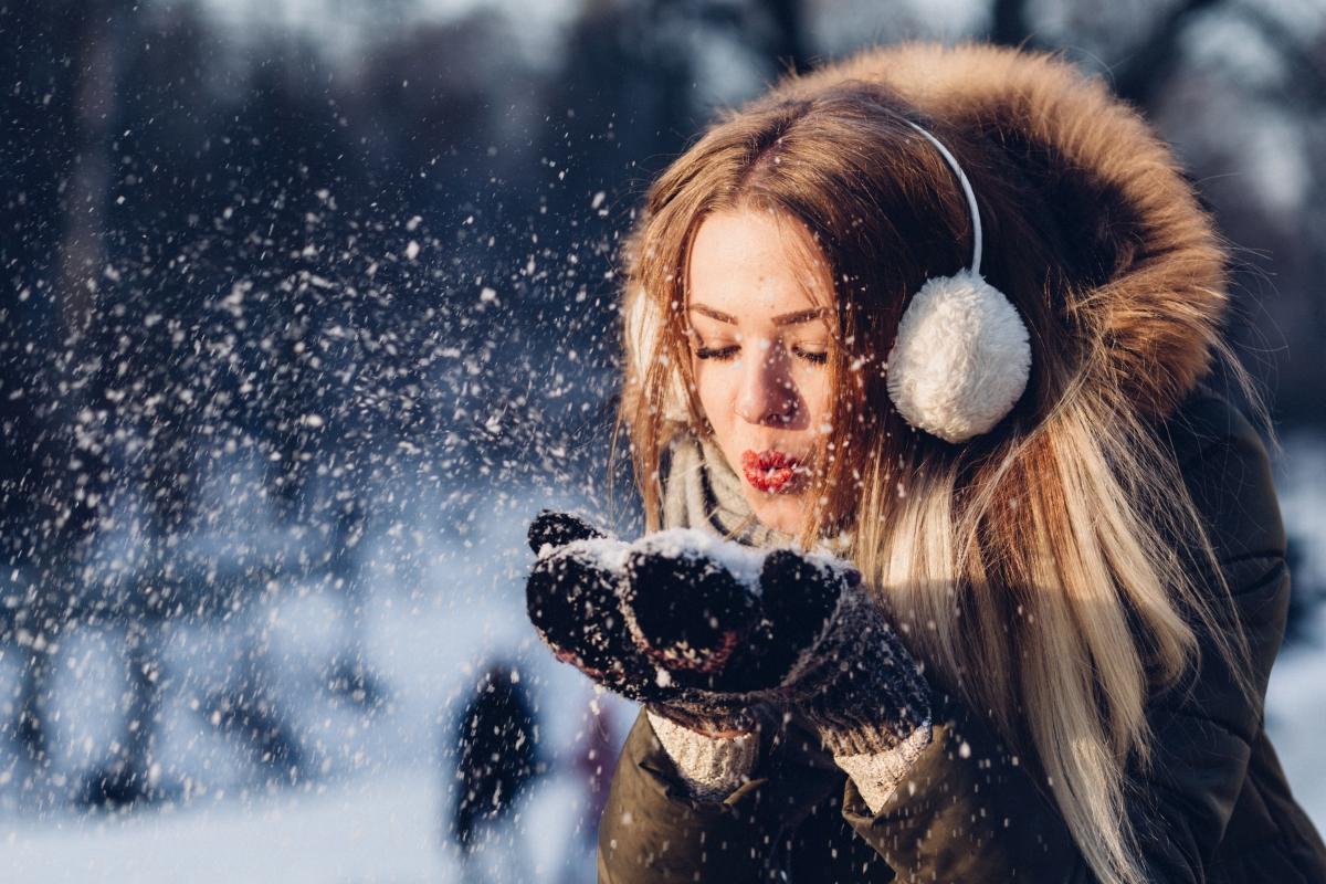 Młoda kobiety dmucha w śnieg zebrany w dłoniach. Kobieta w ciepłej kurtce, nausznikach i rękawiczkach.