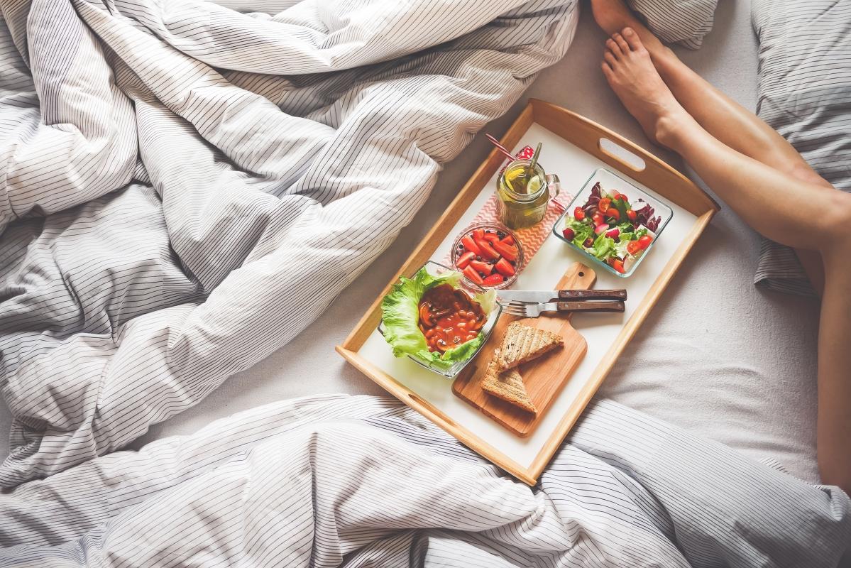 Jak schudnąć bez diety i ćwiczeń? Widok na tacę ze zdrowym śniadaniem i zgrabne, kobiece nogi. Śniadanie w łóżku.