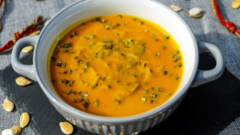 Warzyna zupa krem z posiekanym szczypiorkiem na szarym tle. Obok pestki dyni.