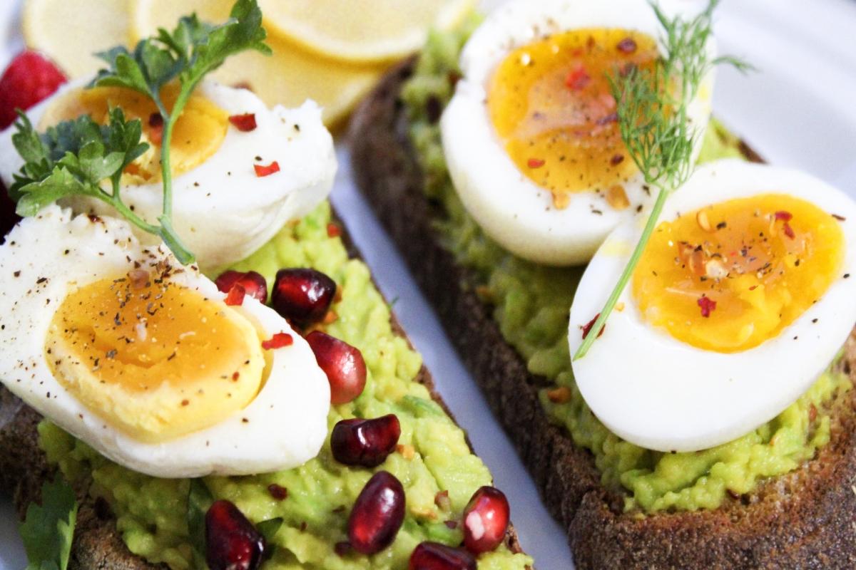 Śniadanie: kanapki z awokado, jajkiem i granatem.