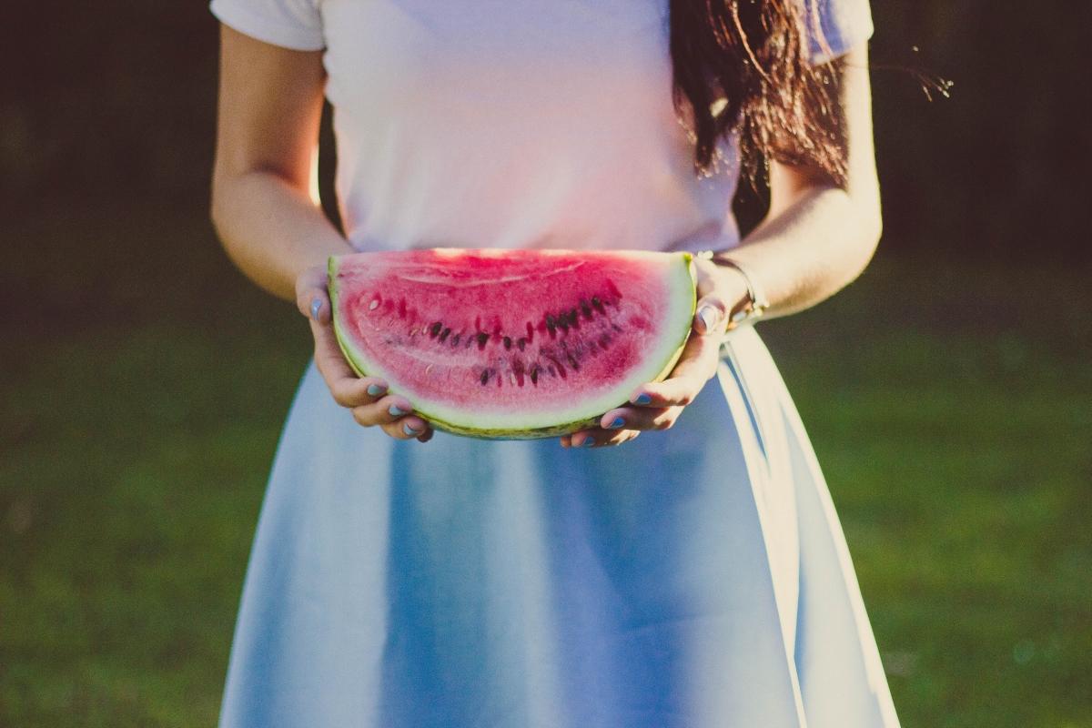 Na zdjęciu zbliżenie na tułów i dłonie kobiety, która trzyma kawałek świeżego arbuza.