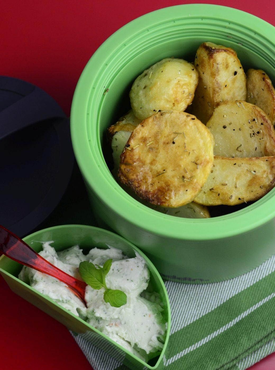 Pieczone ziemniaki z dipem z fety, mięty i chilli. Ziemniaki w lunchboxie, widok od góry.