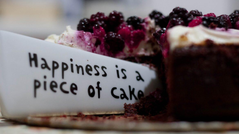 """Tort owocowy z wbitym napisem """"Hapiness is a piece of cake"""" - szczęście to kawałek ciasta!"""