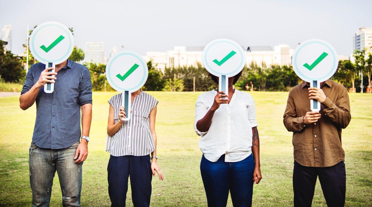4 ludzi trzyma tabliczki z zielonym ptaszkiem oznaczającym akceptację.