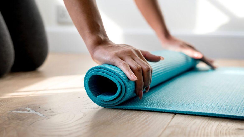 Dietetyczne i fitnessowe trendy 2019. Na zdjęciu dłonie kobiety, która zwija matę do ćwiczeń.