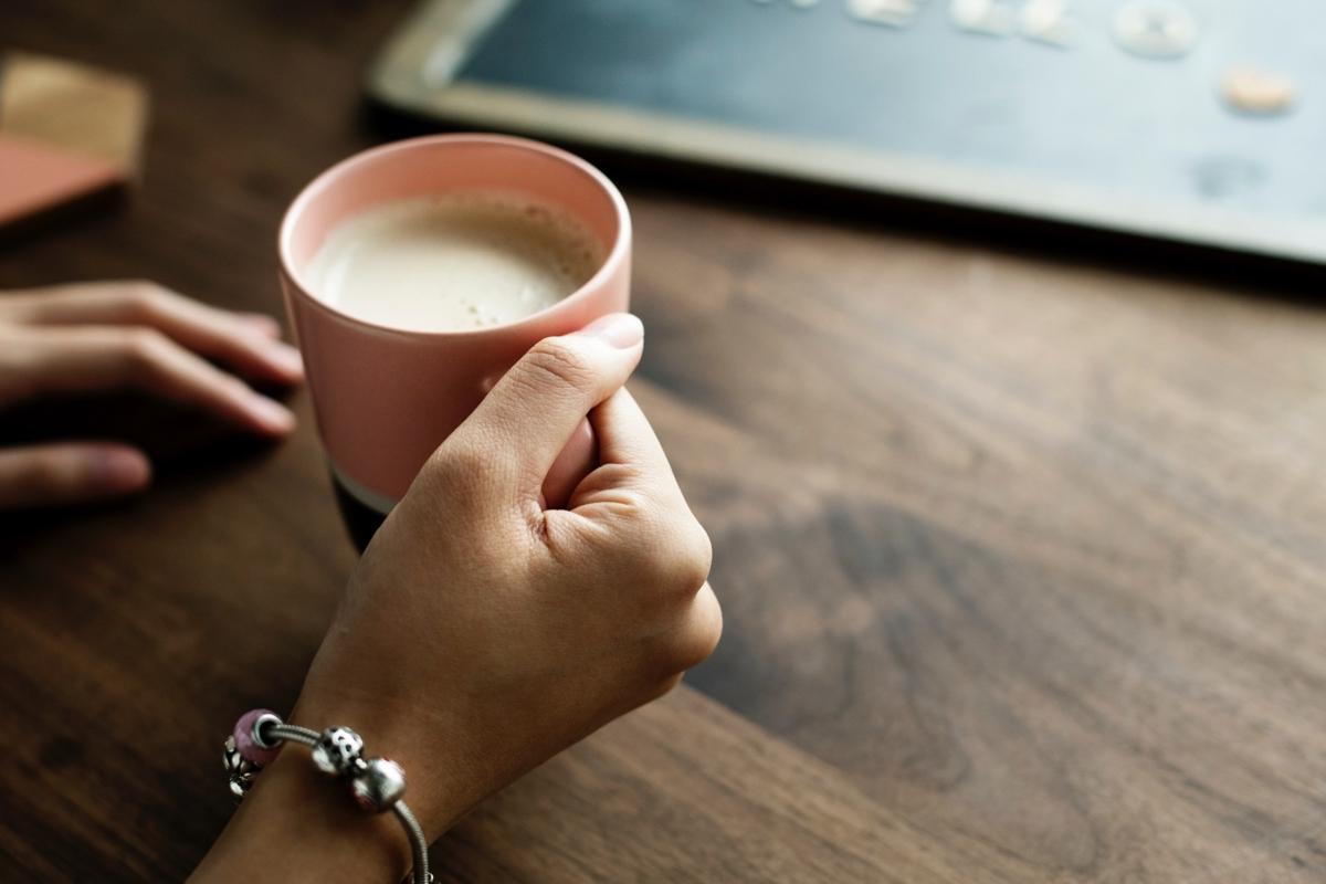 Kobieca dłoń trzyma kubek z kawą z mlekiem bez laktozy. Dolegliwością kobiety jest nietolerancja laktozy.