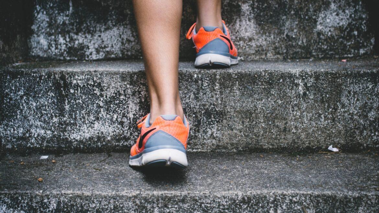 Zbliżenia na buty treningowe na stopach kobiety. Korzyści z aktywności fizycznej, treningu.