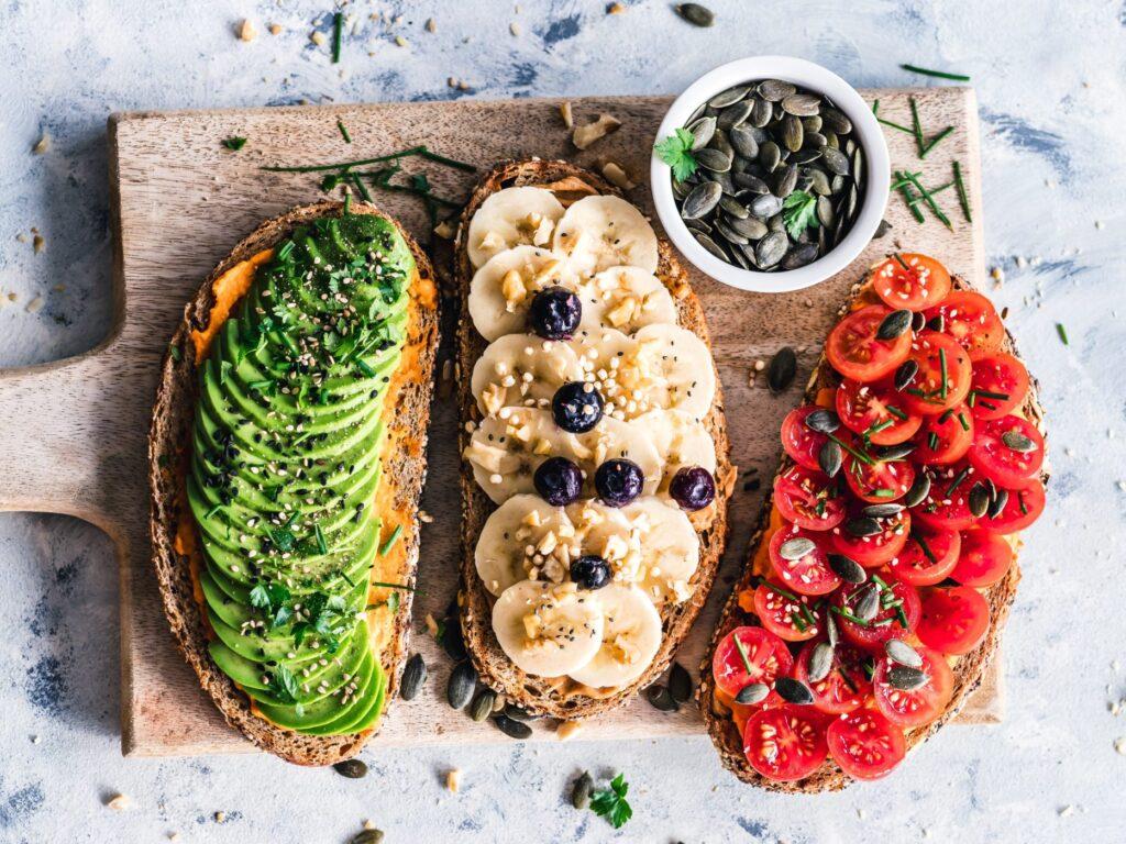 Kanapki wegańskie z bananem, pomidorkami koktajlowymi, awokado, hummusem i pestkami dyni - dieta wegetariańska, dieta wegańska