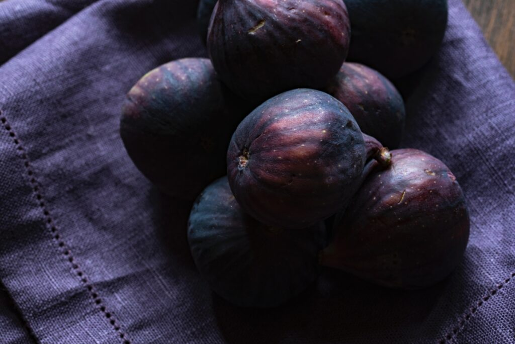 Świeże figi w całości na granatowej ściereczce.