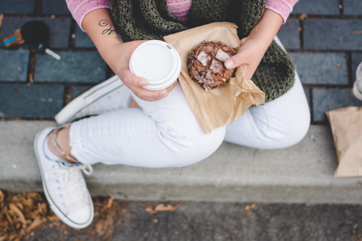 Kobieta cierpi na insulinooporność. Siedzi na schodach, je pączka i pije kawę.