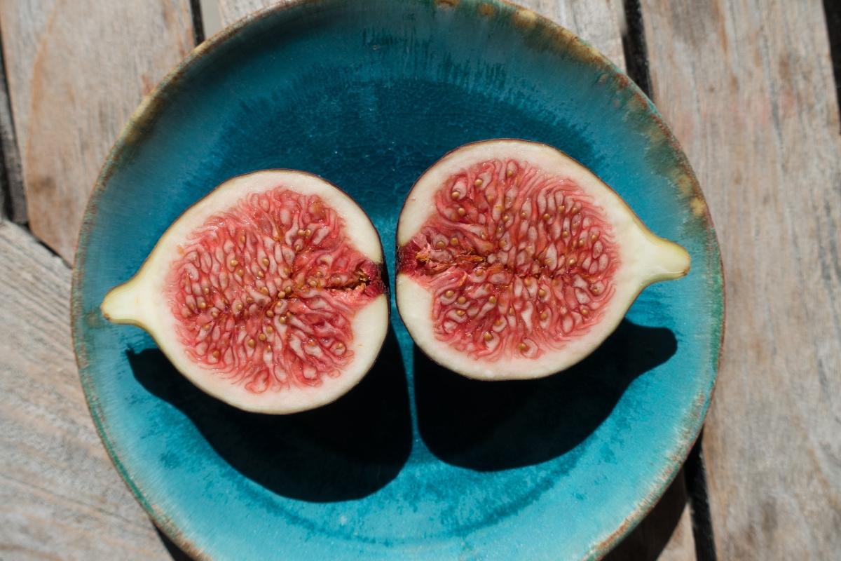 Figa, owoc, przekrojona na pół na niebieskim talerzu.