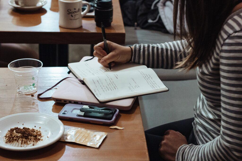 Młoda kobieta robi notatki nadiecie FODMAP
